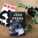 View from above of two books, NO-NO BOY and JOHN OKADA, next to a potted plant on a wooden tabletop